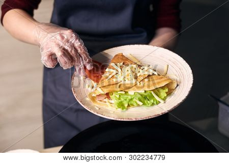 Cropped View Of Chef Decorate In White Plate Sandwich Crepe With Tomato Slice, Green Salad And Grate