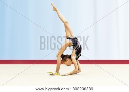 Little gymnast dancing, acrobatic movements, rhythmic gymnastics school, happy sportive childhood poster
