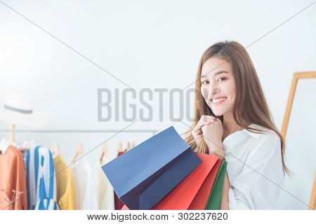 Beautiful Asian Woman Holding Shopping Bags And Smiles At Garments Apparel Clothing Shop. Sale,shopp