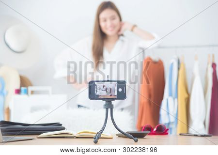 Beautiful Asian Woman Blogger Showing Clothes In Front Of Camera To Recording Vlog Video Live Stream
