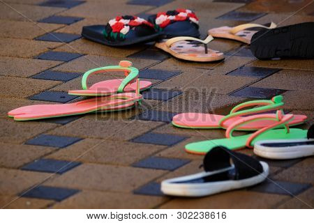 Several Pairs Of Flip-flops Next To Open Pool In Winter