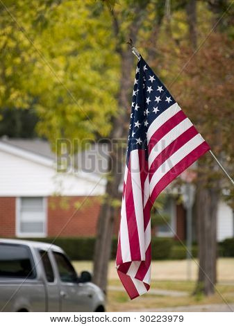 An american flag flying in a suburban neighborhood. poster