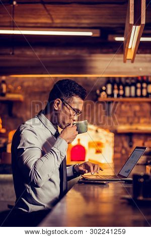 Man Drinking Coffee Near Bar Counter And Working Remotely