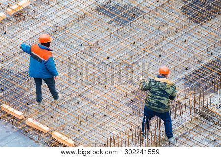People Work With Reinforcement Carcass Made Of Fitness At Construction Site