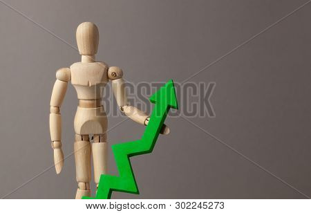 Businessman Is Holding A Green Up Arrow. Deduction In The Rise Of Indicators In The Business At The