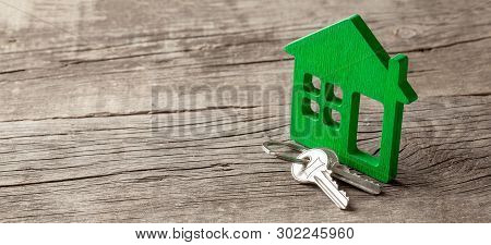 Wooden Green House And Keys On Old Wooden Boards. Copy Space For Text