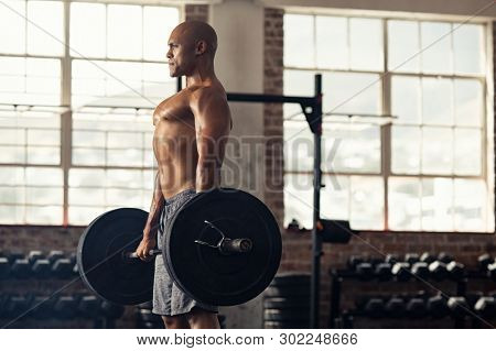 Muscular bald man doing weight lifting exercise at gym with copy space. Side view of fit african american guy standing with heavy weight on barbell at crossfit club. Mature man working on bicep at gym
