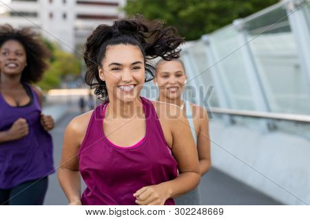 Portrait of happy curvy woman jogging on bridge with friends. Young smiling woman exercising to lose weight with friends. Group of curvy girls running together in bridge.