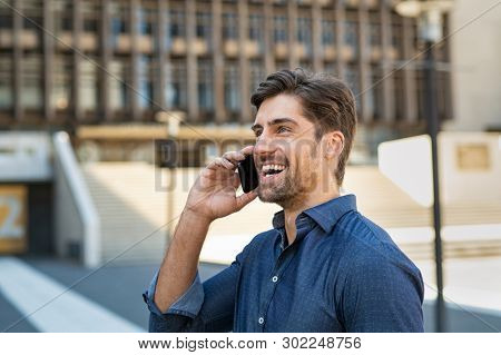 Young man laughing while talking over phone on street. Handsome entrepreneur receiving good news while using smartphone. Cheerful businessman feeling happy over phone and smiling.