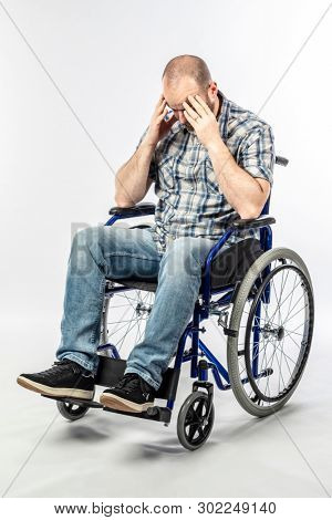 Disabled man in a desperate and sad wheelchair with his head in his hands. Concept of difficulty and resignation.