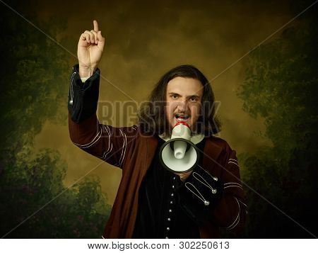 Young Man As A Medieval Knight With The Mouthpiece On Dark Studio Background. Portrait In Low Key Of