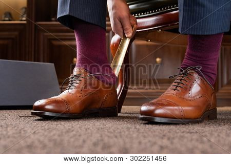Trying new shoes. Man is putting on a new pair of luxury brown full grain leather shoes at footwear store