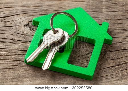 Wooden Green House And Keys On Old Wooden Boards.