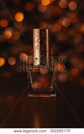 Perfume On The Background Of Golden Bokeh