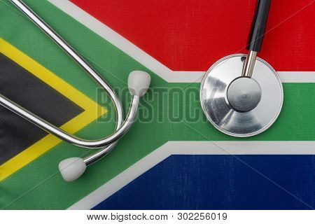 South African Flag And Stethoscope. The Concept Of Medicine. Stethoscope On The Flag In The Backgrou