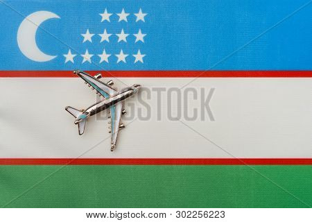 Plane Over The Flag Of Uzbekistan The Concept Of Travel And Tourism. Toy Plane On The Flag In The Ba