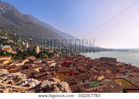 Beautiful View Of Town Malcesine And The Alps Mountains On Lago Di Garda, Skyline View. Veneto, Ital