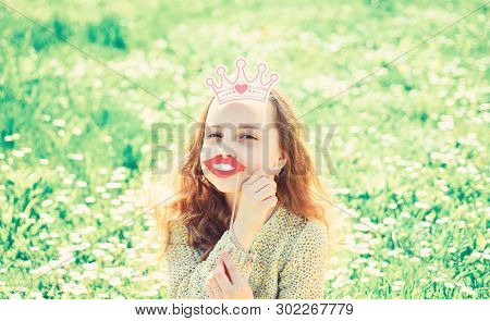 Humour Queen Concept. Girl Sits On Grass At Grassplot, Green Background. Girl On Cheerful Face Spend