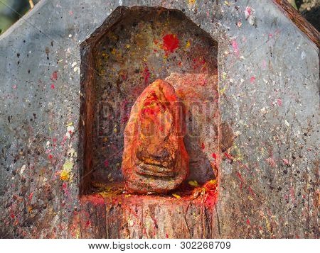 Shrine covered in vermillion to worship Goddess Kali. Red pigment powder on stone, part of Kali Shrine on the mountain in Dhulikhe, Nepal
