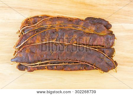 Top view of fresh sour Tamarind with brown shell removed to make Asian sour soup, on wooden background (Tamarindus indica)