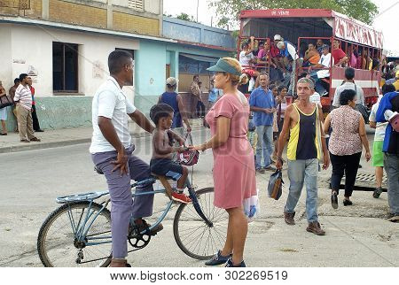 Granma, Cuba-april 04,2016: Streetlife Scene At A Corner In A Ordinary Street With People Sitting In