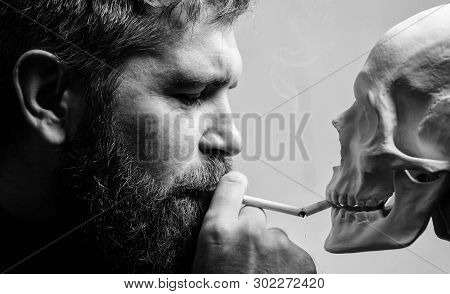 Smoking Cause Health Damage And Death. Man Smoking Cigarette Near Human Skull Symbol Death. Nicotine