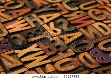 alphabet abstract - vintage wooden letterpress types, stained by color inks, selective focus poster