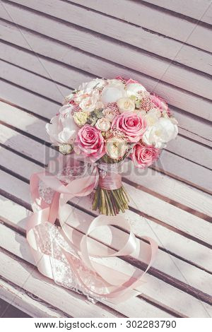 Tender Spring Wedding Bouquet With Pink Lace And Ribbons Lie On A White Wooden Surface. Selective Fo
