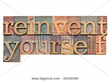 reinvent yourself - personal development concept - isolated text in vintage wood letterpress printing blocks stained by color inks