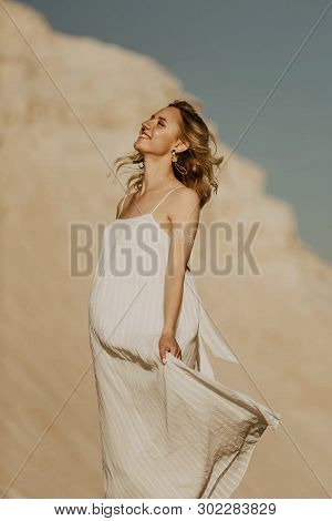 Portrait Of A Beautiful Pregnant Blonde Woman In A White Dress On A Desert Background. Light Sand, S
