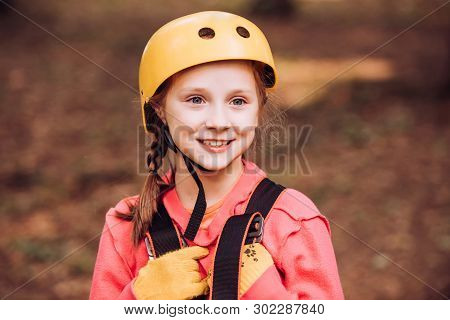 Little Child Climbing In Adventure Activity Park With Helmet And Safety Equipment. Happy Child Climb