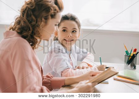 Cheerful Child Looking At Beautiful Mother While Doing Homework Together