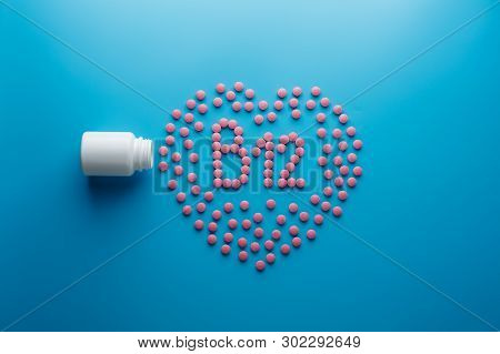 Pink Tablets In The Form Of Vitamins B12 In The Heart On A Blue Background, Spilled From A White Can