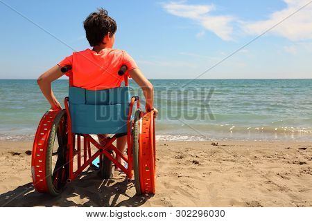 Beach And A Young Boy On The Wheelchair By The Sea In Summer