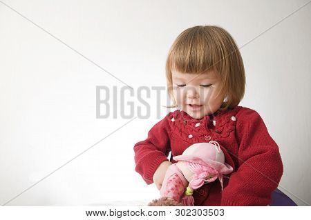 Little Girl Playing With Doll Smiling Happy. Cute Caucasian Baby