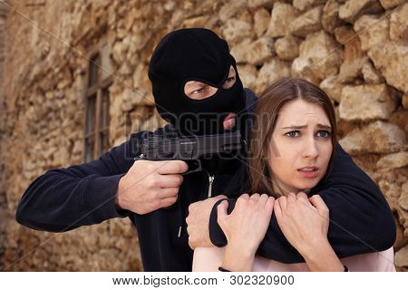 Masked Man With Gun Holding Woman Hostage  Outdoors. Criminal Offence