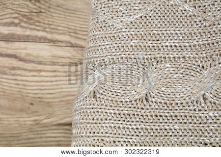 Pile of knitted winter clothes on wooden background, sweaters, knitwear, space for text poster