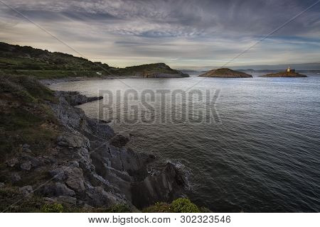 Dusk At Bracelet Bay High Tide At Bracelet Bay And Mumbles Lighthouse On The Gower Peninsula In Swan