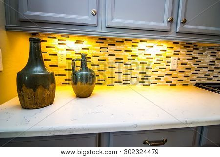Two Decorative Jugs On Kitchen Counter With Backsplash