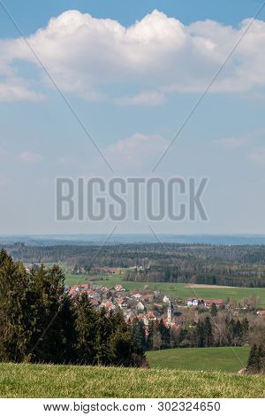Little Village In The Middle Of The German Countryside With Hills, Forests, Fields And Meadows