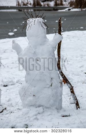 White Snowman Mit A Wooden Stick And Hair Made Of Dry Grass