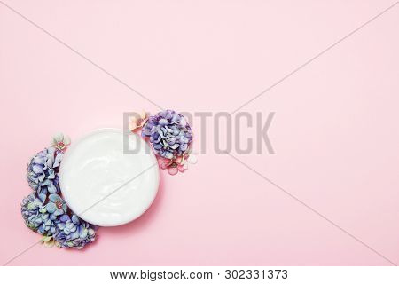 A Jar Of Cream With Flowers On A Pink Background. Top View.