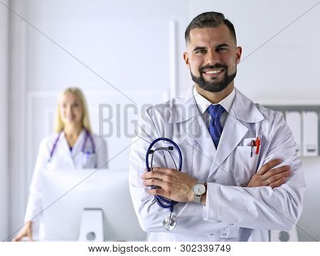 Handsome Smiling Male Doctor. Welcome To Our Clinic. Confident Physician. Office Background. Man Pra