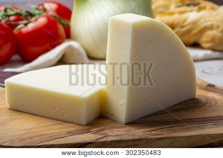 Italian Cheese, Provolone Dolce Cow Cheese From Cremona Served With Olive Bread And Tomatoes Close U