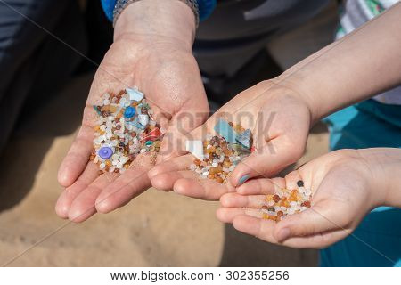 Family Of Mother And Children Holding And Showing Small Tiny Harmful Plastic Beads Collected On The
