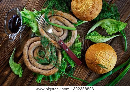 Grilled Sausages, Corn Buns, Transparent Sauceboat And Fork Lie On A Wooden Surface With Greens: Let