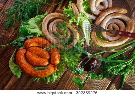 Grilled Sausages And Transparent Sauceboat Lie On A Wooden Surface In The Sun Along With Greens: Let