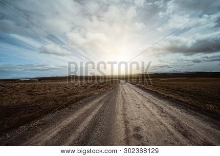 Empty Dirt Road Through Countryside Landscape.