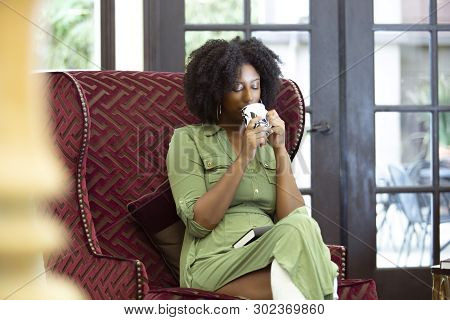 Black African American Woman Resting At Home Drinking Coffee Or Cbd Tea While Relaxing On A Chair.