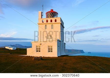 Gorgeous landscape with white lighthouse at Cape Dyrholaey, located on south coast of Atlantic ocean in Iceland